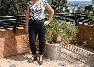 Modeling skinny jeans made from the Liana Stretch Jeans sewing pattern on a terrace with a city view .