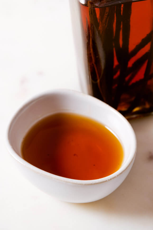 Photo of a small bowl and a glass bottle with homemade vanilla extract
