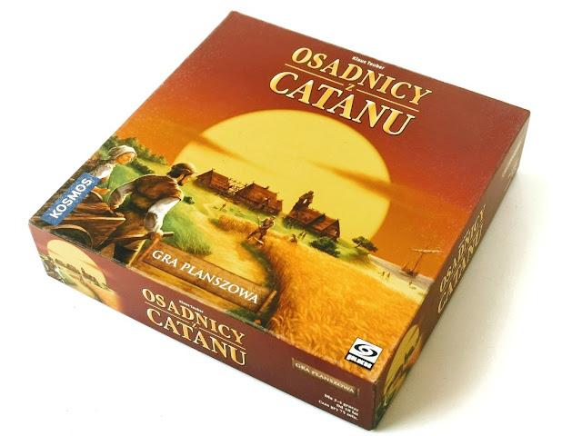 na zdjęciu pudełko gry osadnicy z catanu a na nim ilustracja ludzi idących pomiędzy polem a łąką w kierunku wioski, w tle widać zachodzące słońce