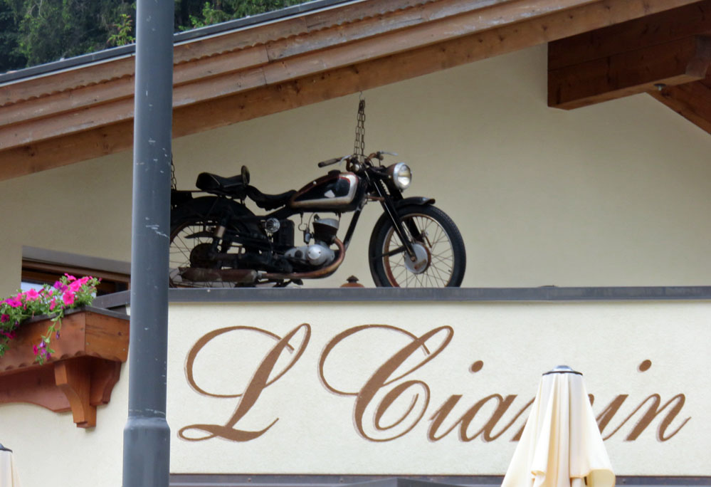 Motorcycle near roof of restaurant as display.