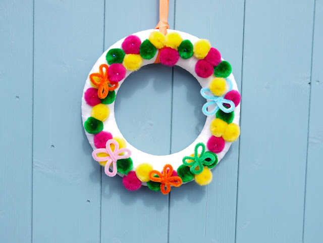 a white wreath decorate with orange and blue flowers and pink, yellow, and green pom poms hangs on a blue door