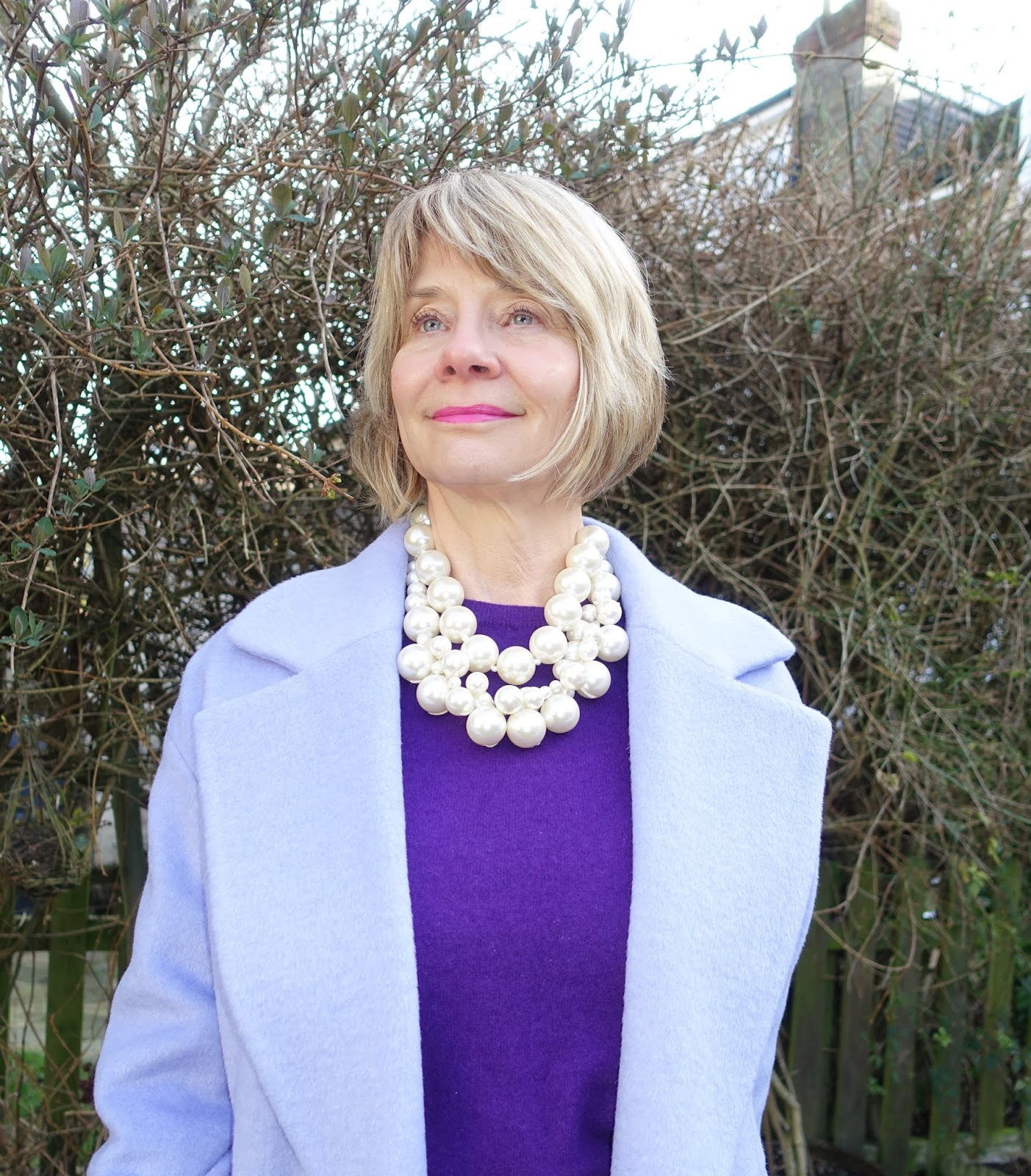 Gail Hanlon from Is This Mutton in lilac cashmere coat, purple jumper and layered chunky pearl necklaces