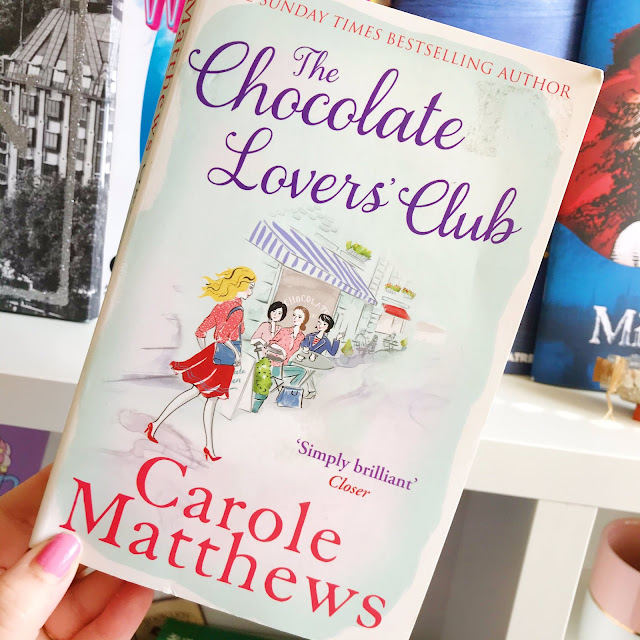 The Chocolate Lover's Club by Carole Matthews held up in front of desk