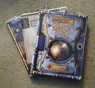 Three gaming books - the Dungeon Master's Guide, the Forgotten Realms Campaign Setting, and the Players Handbook