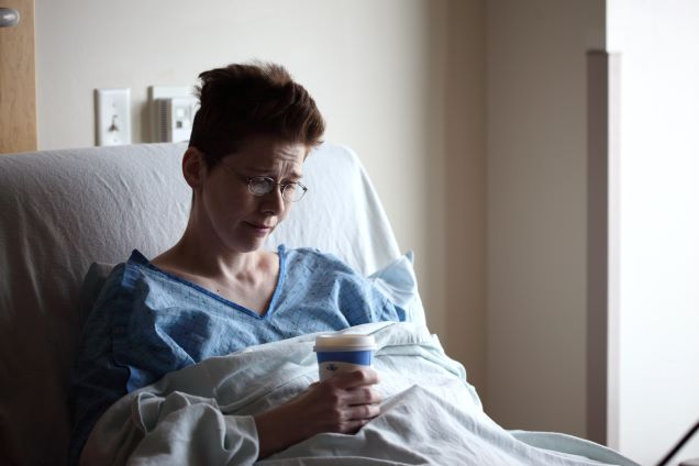 Sick woman on her bed with cup