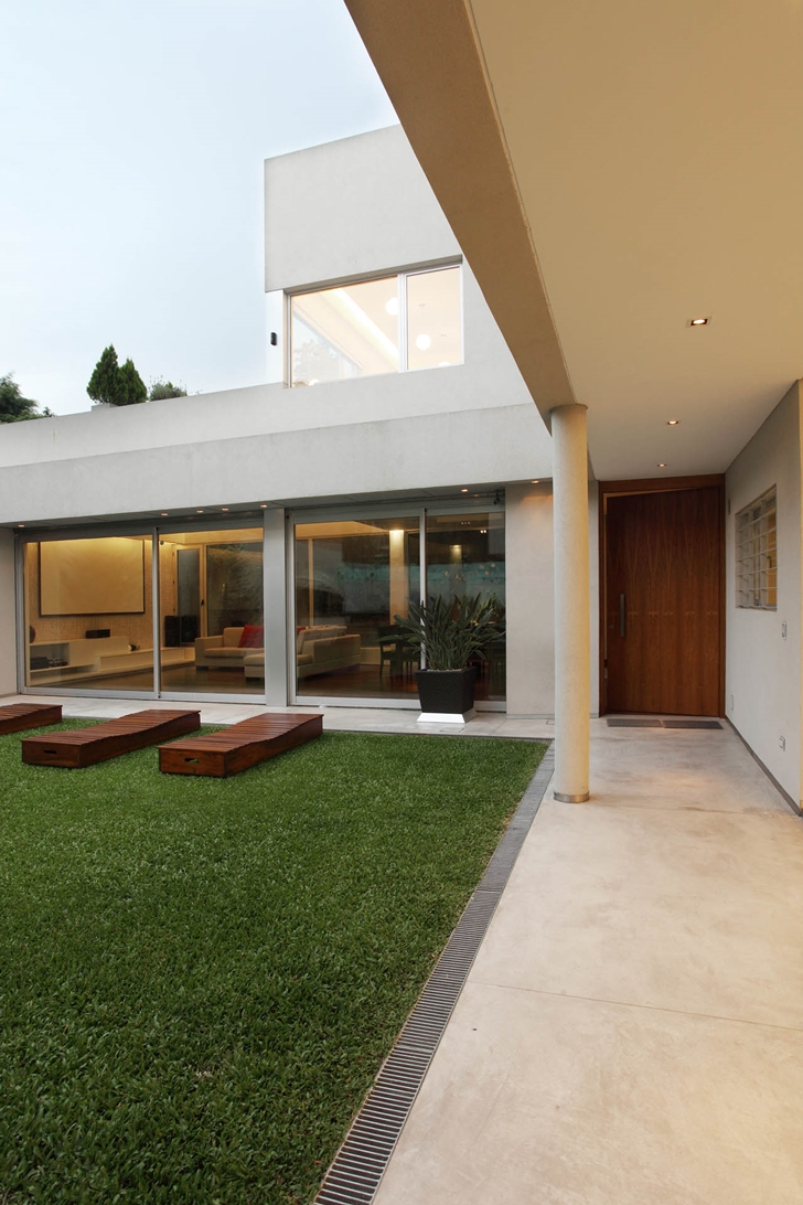 Grass in the backyard of Modern Villa Devoto by Andres Remy Architects