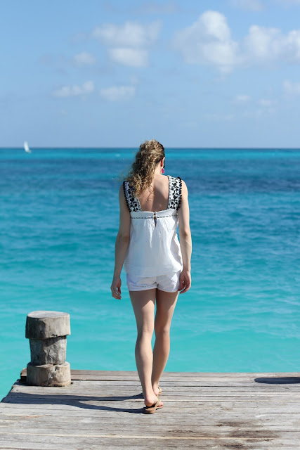 Simple beach outfit with embroidered pom pom tank and white shorts