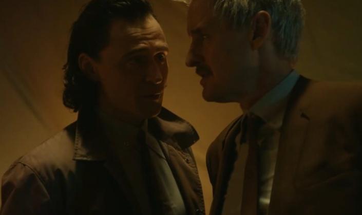 Imagem: Loki (homem branco de cabelo preto na altura do ombro e casco marrom claro) e Mobius (homem branco de cabelo curto e branco, que usa terno marrom escuro) estão se encarando, loki está falando algo e com expressão de preocupação, mobius está de lado e olha fixo para para o lado.