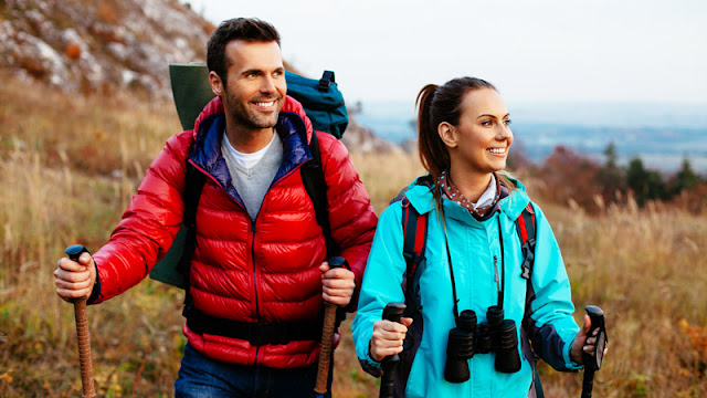 a pair of geared-up hikers smiling while looking into the distance