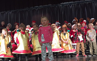 Students dressed as gold bells signing for Christmas program