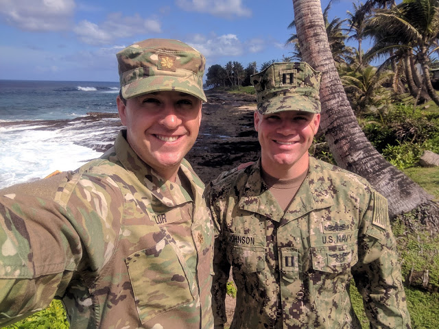 two men in military uniform in a tropical location