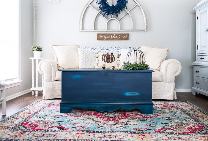 multicolor rug, blue painted blanket chest, white sofa, antique arch window and blue berry wreath