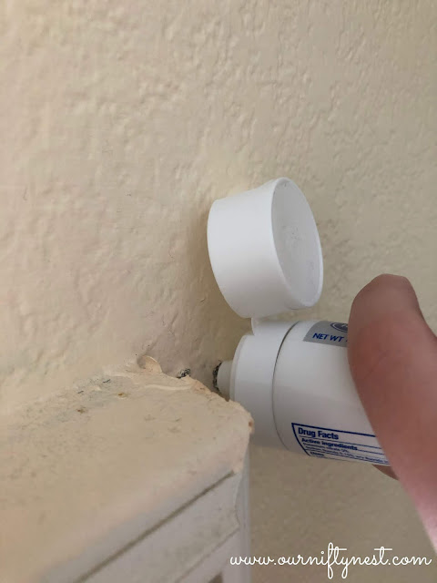 squeezing toothpaste in the hole in the drywall