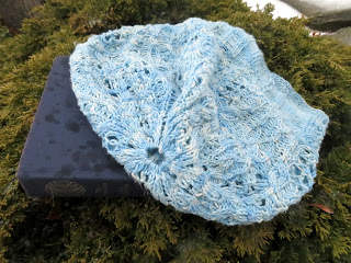A fingering-weight cable and lace beanie hat laying flat.  The hat has a lengthy ribbed rib that flows into intricate cables and lace.