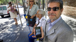 Fotografía de varias personas en una parada de autobús probando la app
