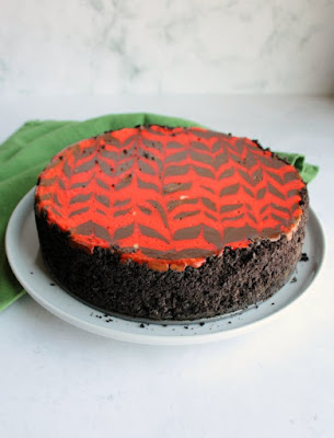 whole chocolate cheesecake with red zig zag pattern baked in