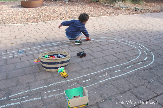 Toddler playing on chalk car track