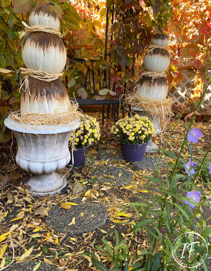 Unique Rust Paint Dripped Abstract Pumpkin Topiaries with white artificial stacked pumpkins and rust activated paint to decorate outdoors for fall.