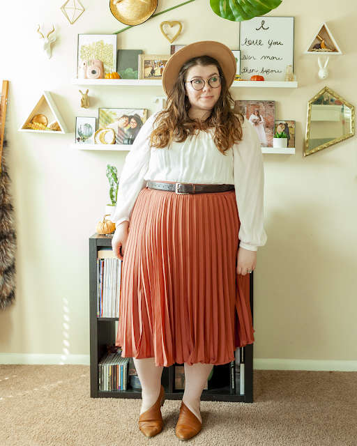 An outfit consisting of camel brown wide brim hat, a white long poet sleeve square neck blouse tucked into a rose colored pleated midi skirt, belted with a brown belt and cognac brown d'orsay flats.
