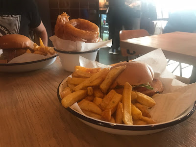 two burgers and a bowl of onion rings on a table