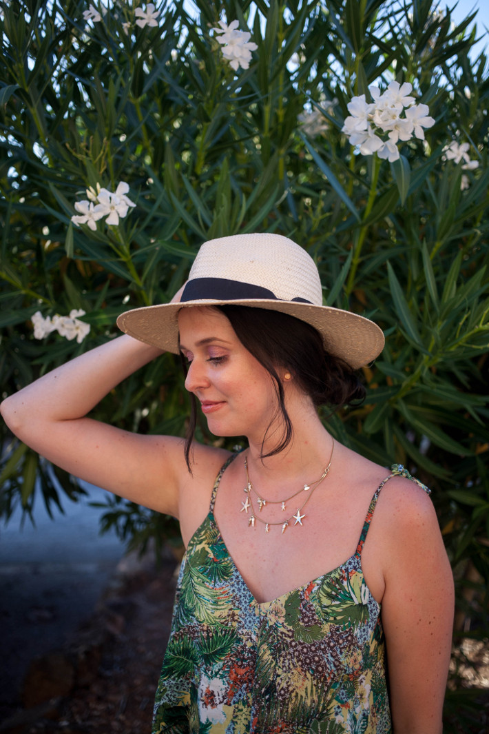 panama hat, seashell necklace, jungle print dress