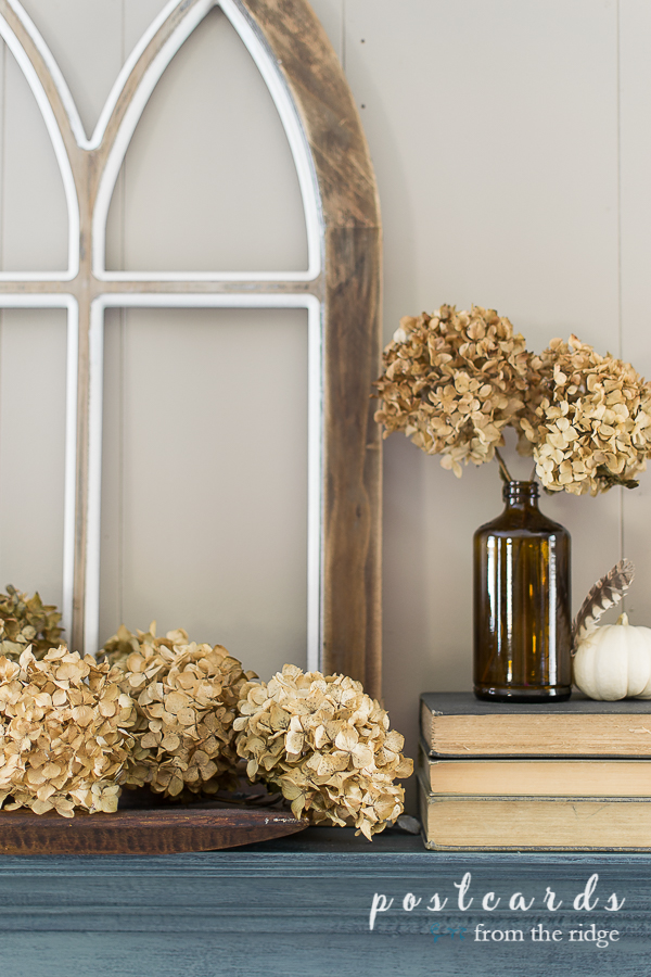 brown bottle and dried hydrangeas with cathedral window on fireplace mantel