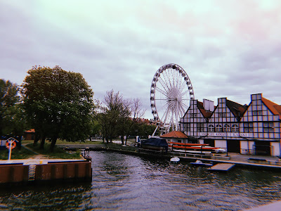 big wheel and some buildings on the waterfront in Gdansk with some trees and a grey sky