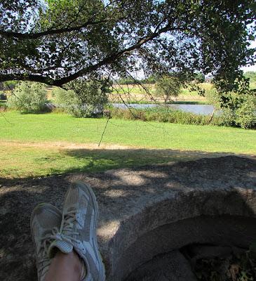 pés cruzados sobre um muro e lago ao fundo