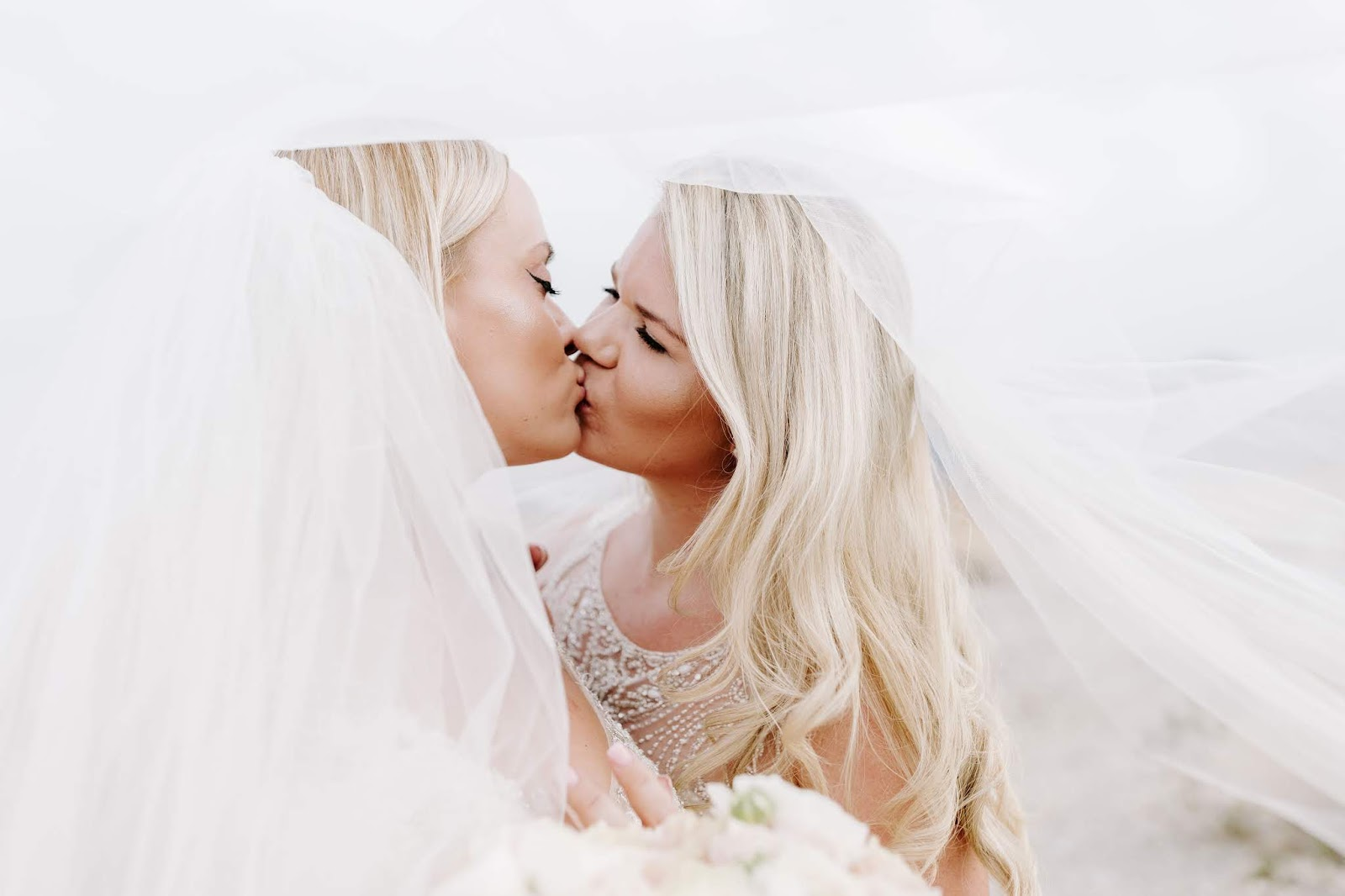 Whitney and Megan kiss as brides with a veil