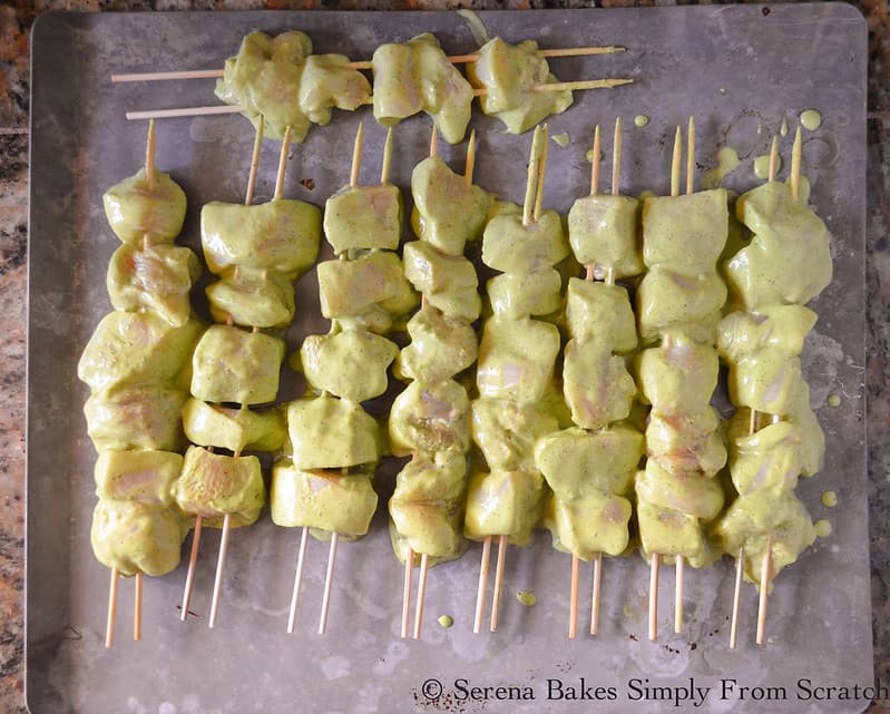 Green Curry Yogurt Marinaded Chicken placed on wooden skewers on cookie sheet.