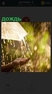 Идет дождь и из под зонта протянута рука и собирает воду, которая льется с зонтика