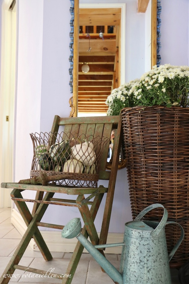 French Country rustic fall entry with mums and variegated green gourds in a chippy green wooden chair