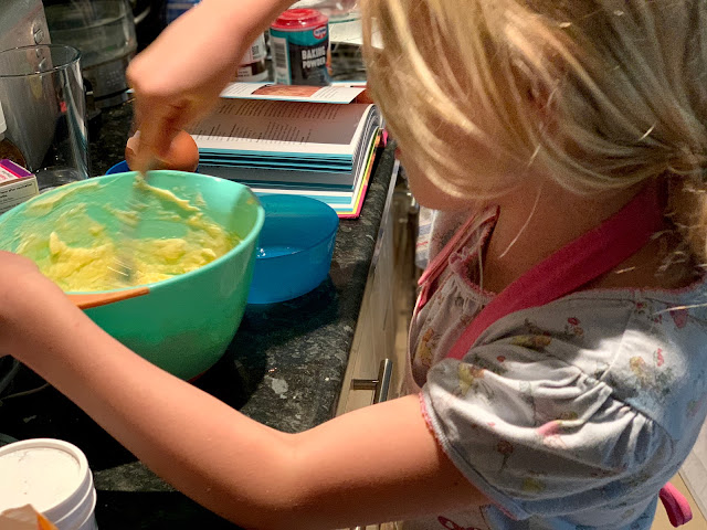 7 year old mixing together dairy free spread and sugar in her night dress for victoria sponge