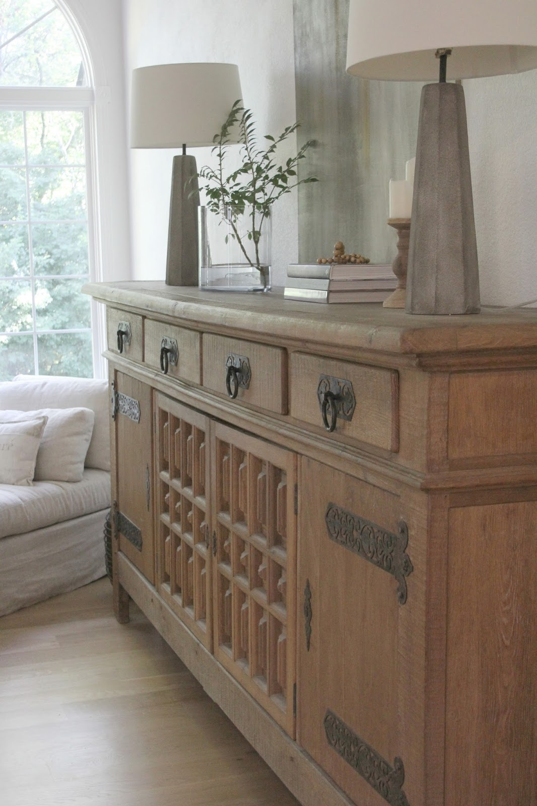 Rustic oak Belgian antique cupboard in European country styled living room by Hello Lovely Studio.  Come see: Best White Paint Colors: 6 Favorites Designers Turn To in case you need paint color ideas. #hellolovelystudio #europeancountry #livingroom