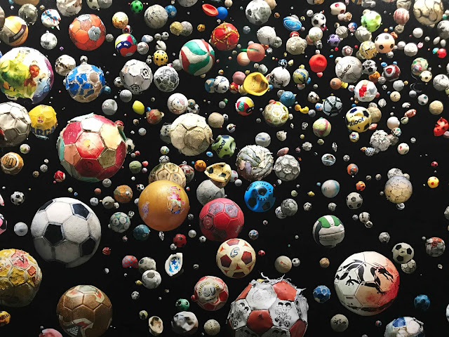 Hundreds of broken colourfull plastic soccer balls in front of a black canvas.