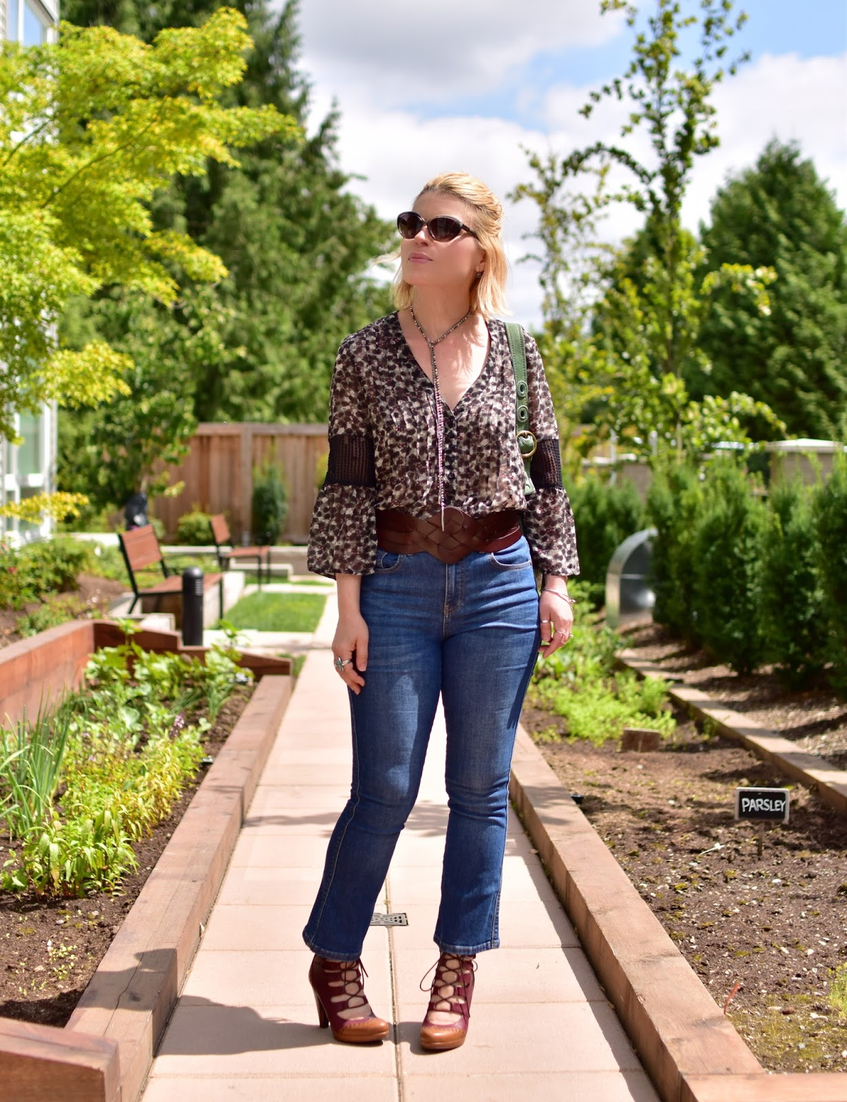 Monika Faulkner styles cropped flare jeans with a floral peasant blouse, lace-up heels, and a corset belt