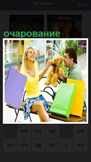 Мужчина очарован женщиной, с которой сидит на скамейке с покупками