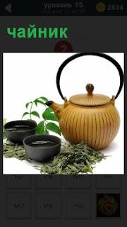На столе расположены две чашки и чайник для заварки чая, рядом листья в качестве крепкого отвара
