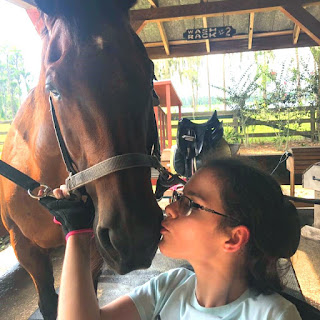 On the left of the frame, a brown horse looks at the camera. On the right of the frame, Bryanna extends a hand toward the horses face, kissing him on the nose