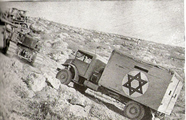 A bulldozer towing a truck on the steep Burma road, June 1948