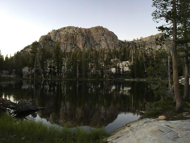 granite crag rises above trees and lake at dusk