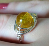 A silver wire ring with a yellow bead