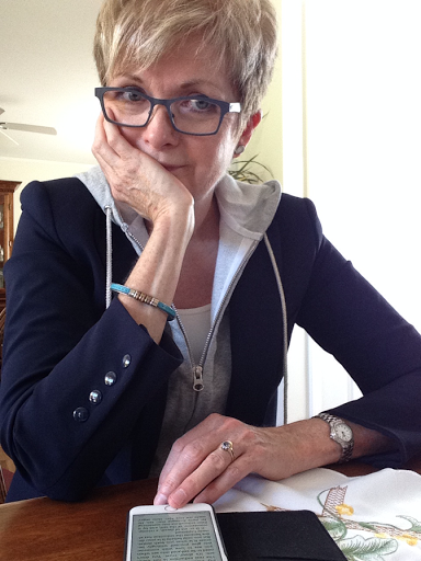 woman looking at cell phone over her glasses