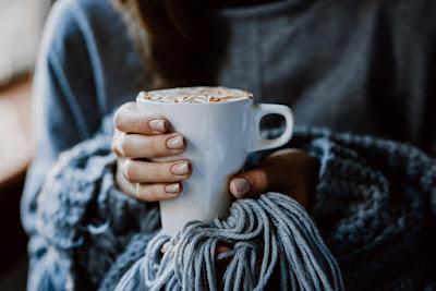Chica sosteniendo una taza de café de una cafetería de Reikiavik