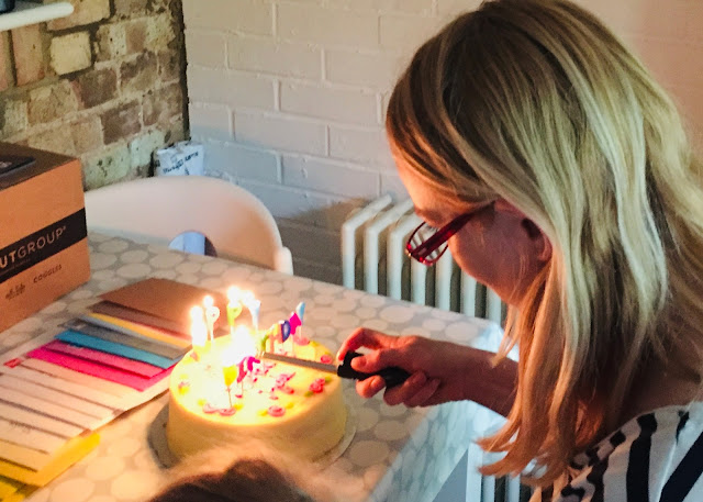 lighting  a birthday cake candle with a row of cards in front