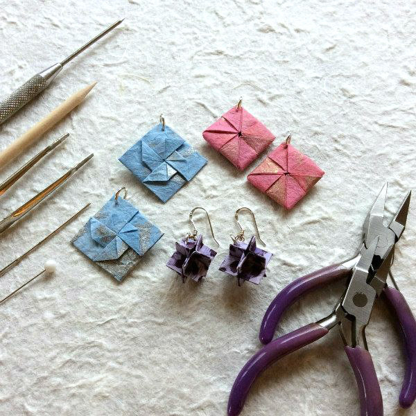 three pairs of origami paper earrings with tools to make them