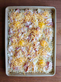 sheet pan filled with hash browns, bacon, eggs and cheese ready to go in oven