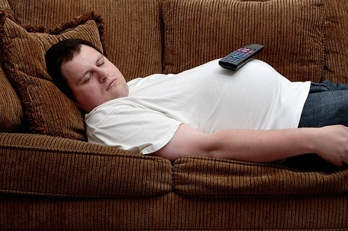 Obese man sleeping on a couch