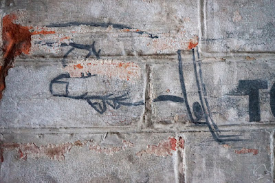 A small section of a red brick wall, painted grey-white wiht a painted outline of a pointing hand, incuding fingernail and cuff details.