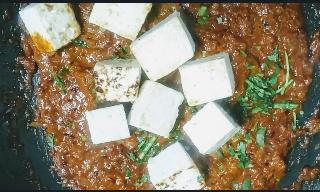 Pouring fried paneer into the gravy for paneer masala recipe